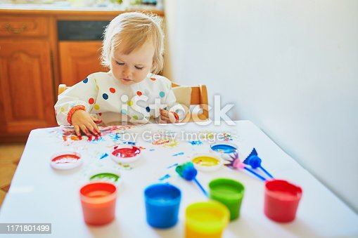 istock Adorable little girl painting with fingers 1171801499