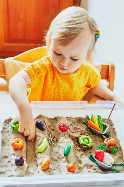 Adorable little girl playing with toy fruits and vegetables stock photo