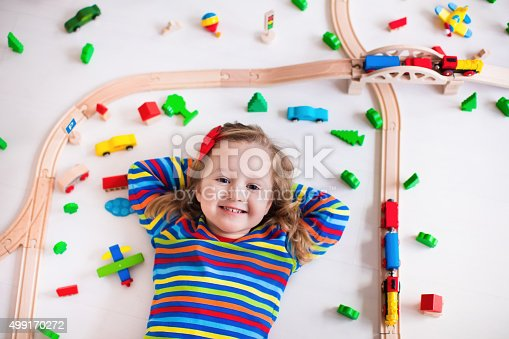 500939056 istock photo Adorable little girl playing with wooden trains 499170272