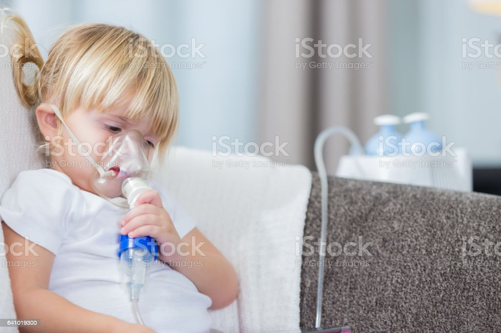 Adorable little girl receives breathing treatment stock photo