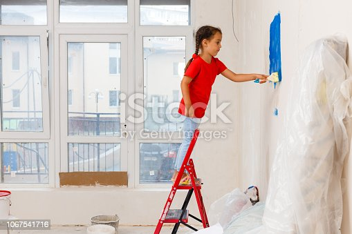 Adorable little girl repairing wall in apartment, concept of easy home renovating