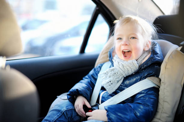 Adorable little girl sitting in a car seat stock photo
