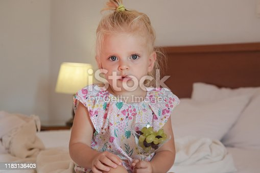 Adorable little girl sitting on a bed and eating grapes from a bowl