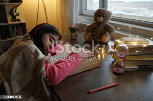 Adorable little girl sleeping on a stack of books over