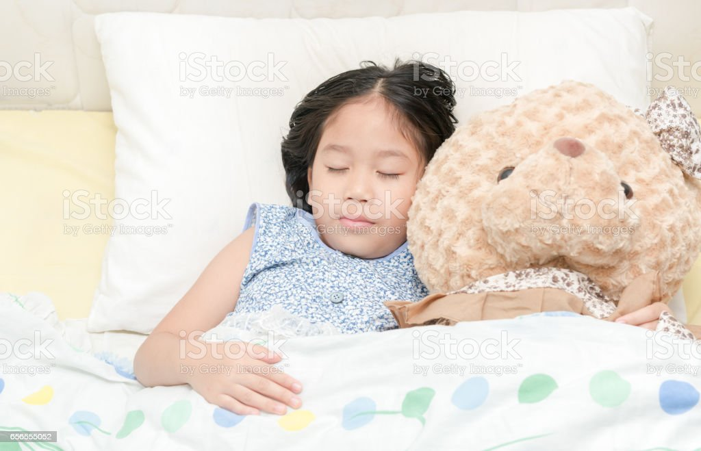 1ea5bd48e18a Adorable little girl sleeping on the bed with her teddy bear - Stock image .