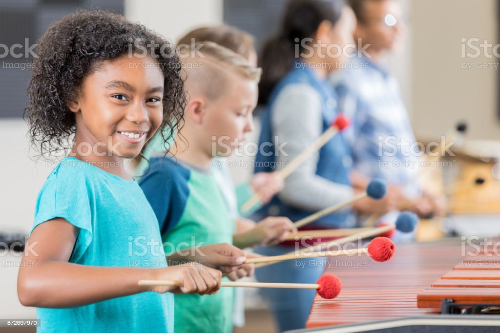 Adorable little girl smiles for camera while playing xylophone stock photo