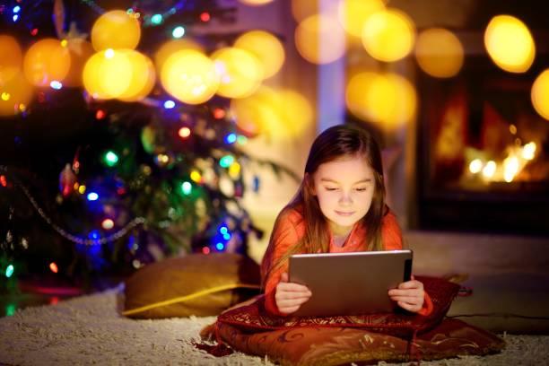 entzückende kleine mädchen mit einem tabletpc durch einen kamin auf weihnachtsabend - kinder weihnachtsfilme stock-fotos und bilder