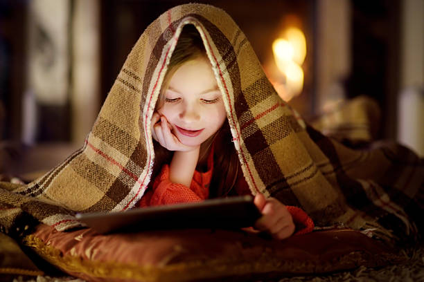 adorable little girl using tablet by fireplace on christmas evening - christmas movie foto e immagini stock