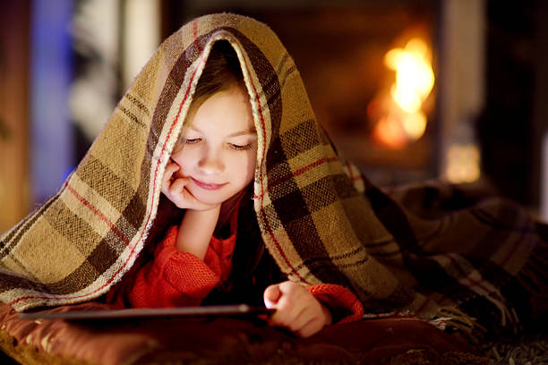 adorable little girl using tablet by fireplace on christmas evening - kinder weihnachtsfilme stock-fotos und bilder