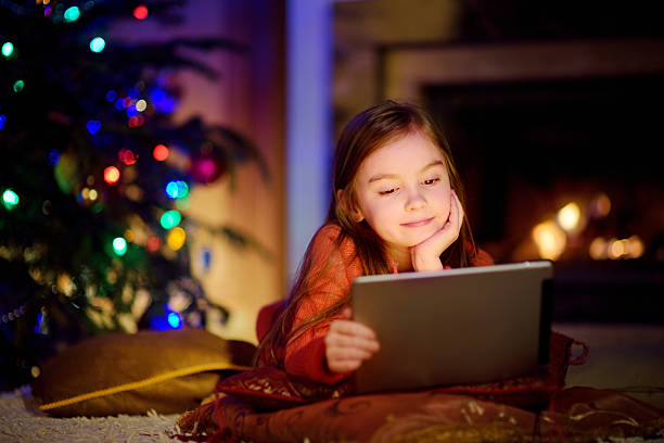 adorable little girl using tablet pc by fireplace on christmas - weihnachts video stock-fotos und bilder