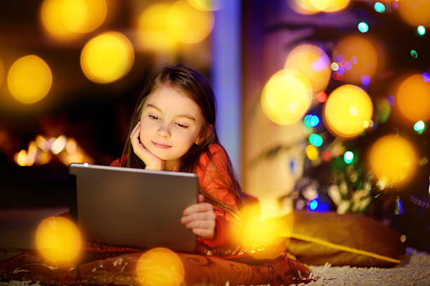adorable little girl using tablet pc by fireplace on christmas - weihnachten videos stock-fotos und bilder