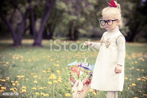 istock Adorable little girl walking on the dandelion field. 476702748