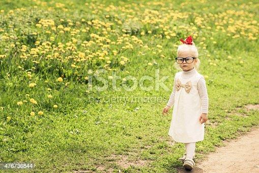 istock Adorable little girl walking on the dandelion field. 476736844
