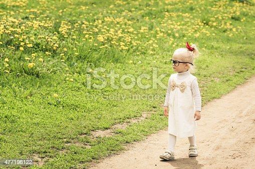 istock Adorable little girl walking on the dandelion field. 477196122