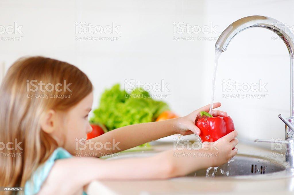 Adorable little girl washing vegetables stock photo