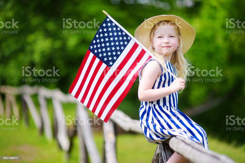 Adorable little girl wearing hat holding american flag outdoors on beautiful summer day stock photo