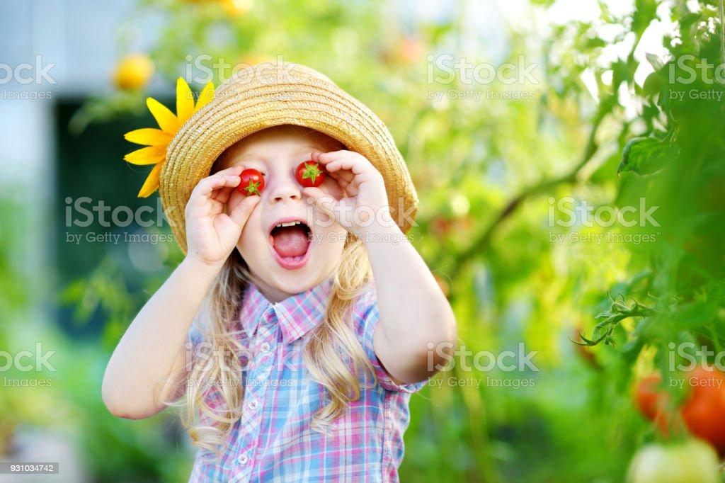 Entzückende kleine Mädchen tragen Hut Kommissionierung frische reifer Bio-Tomaten im Gewächshaus – Foto