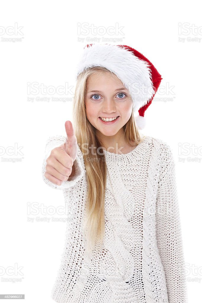 Adorable little girl wearing Santa hat gesturing thumbs up sign royalty-free stock photo