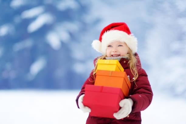 Entzückende kleine Mädchen trägt Santa Hut hält einen Haufen von Weihnachtsgeschenken an schönen Wintertag – Foto