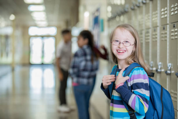 Adorable little girl with Down Syndrome smiles on her first day of Junior High School Adorable little girl with Down Syndrome smiles on her first day of Junior High School cute middle school girls stock pictures, royalty-free photos & images