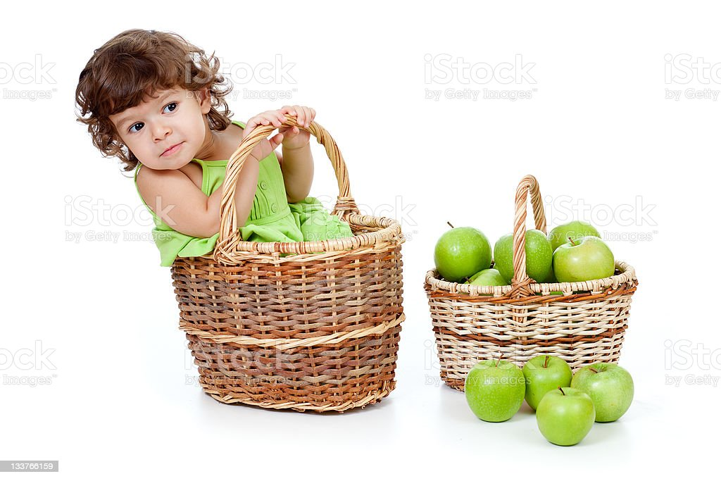 Adorable little girl with green apples in basket isolated studio royalty-free stock photo