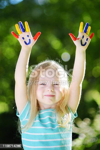 123499844 istock photo Adorable little girl with her hands painted having fun outdoors 1158714286