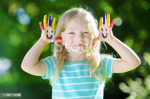 123499844 istock photo Adorable little girl with her hands painted having fun outdoors 1158714288