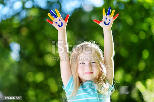 123499844 istock photo Adorable little girl with her hands painted having fun outdoors 1160097852