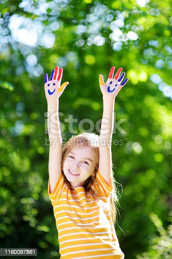 123499844 istock photo Adorable little girl with her hands painted having fun outdoors 1160097861