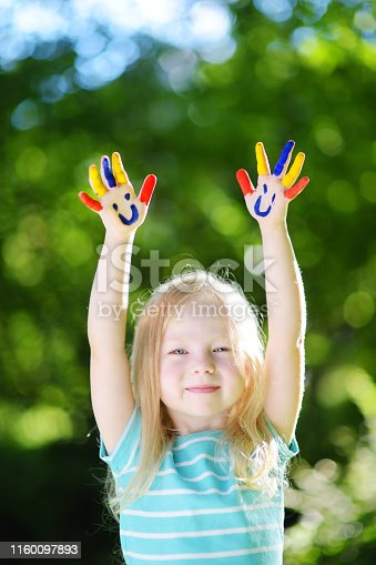 123499844 istock photo Adorable little girl with her hands painted having fun outdoors 1160097893