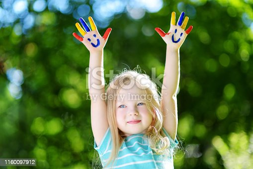 123499844 istock photo Adorable little girl with her hands painted having fun outdoors 1160097912