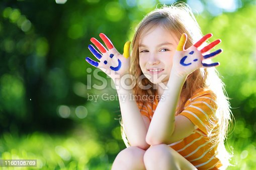 123499844 istock photo Adorable little girl with her hands painted having fun outdoors 1160108769