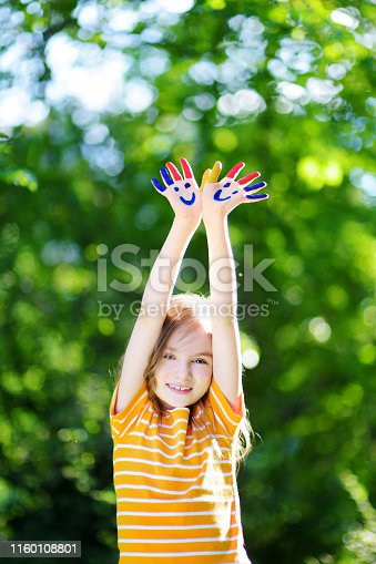 123499844 istock photo Adorable little girl with her hands painted having fun outdoors 1160108801