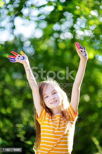 123499844 istock photo Adorable little girl with her hands painted having fun outdoors 1160178982