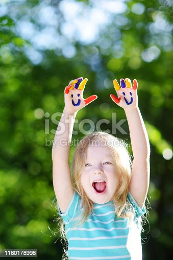 123499844 istock photo Adorable little girl with her hands painted having fun outdoors 1160178998