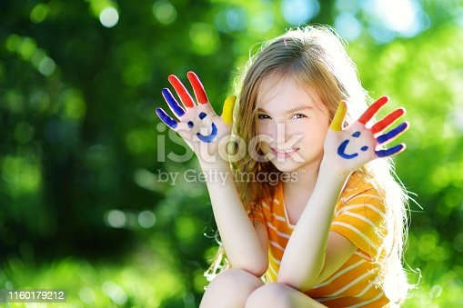 123499844 istock photo Adorable little girl with her hands painted having fun outdoors 1160179212