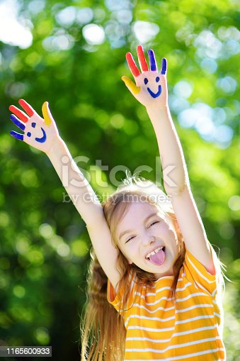 123499844 istock photo Adorable little girl with her hands painted having fun outdoors 1165600933