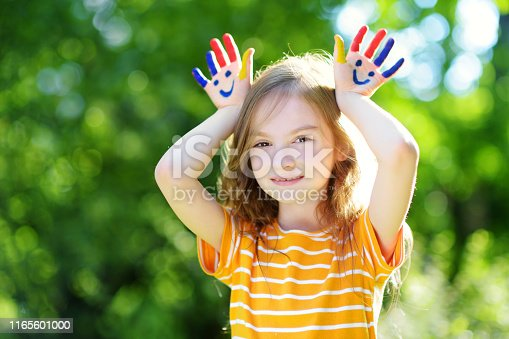 123499844 istock photo Adorable little girl with her hands painted having fun outdoors 1165601000