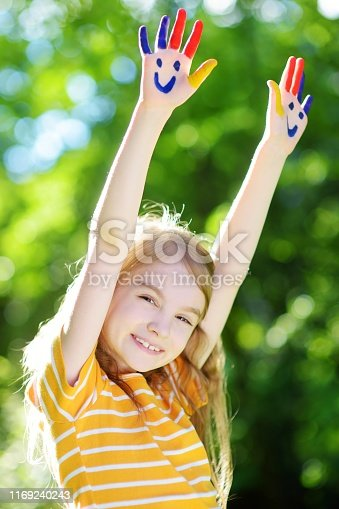 123499844 istock photo Adorable little girl with her hands painted having fun outdoors 1169240243