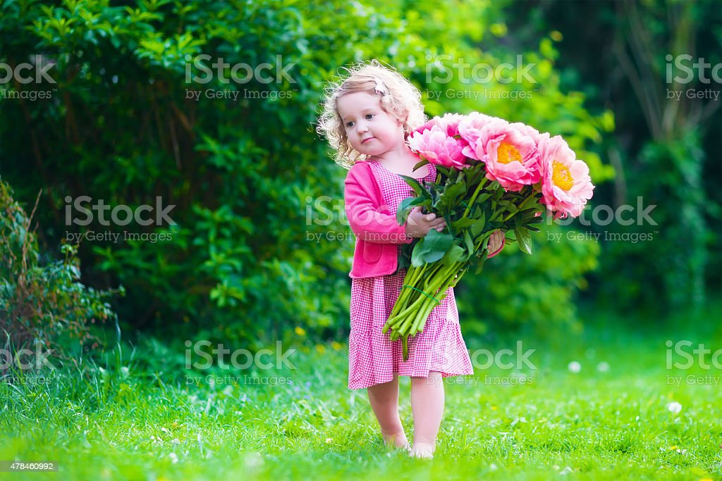 Little cute girl with peony flowers. Child wearing a pink dress...