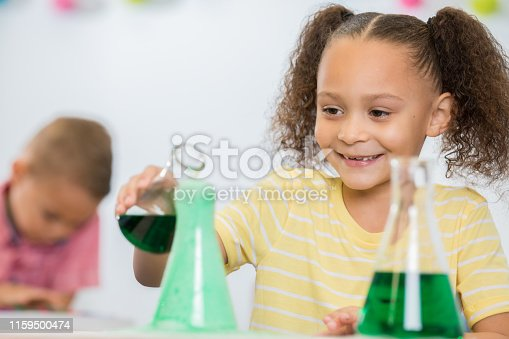 istock Adorable little girl with pigtails is smiling while doing a simple chemistry experiment in STEM class 1159500474