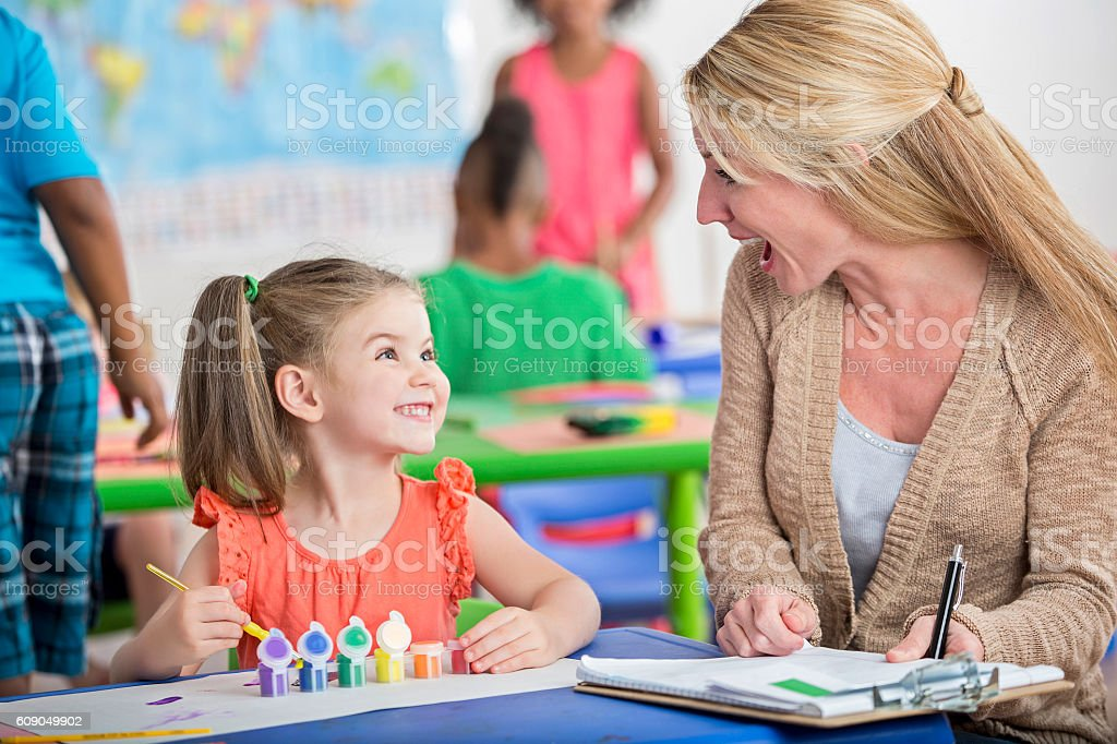 Adorable little girl with pigtails painting a picture in daycare stock photo