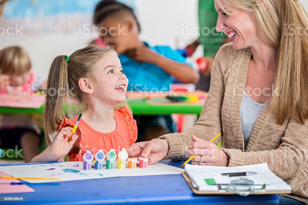Adorable little girl with pigtails playing with paints in daycare stock photo