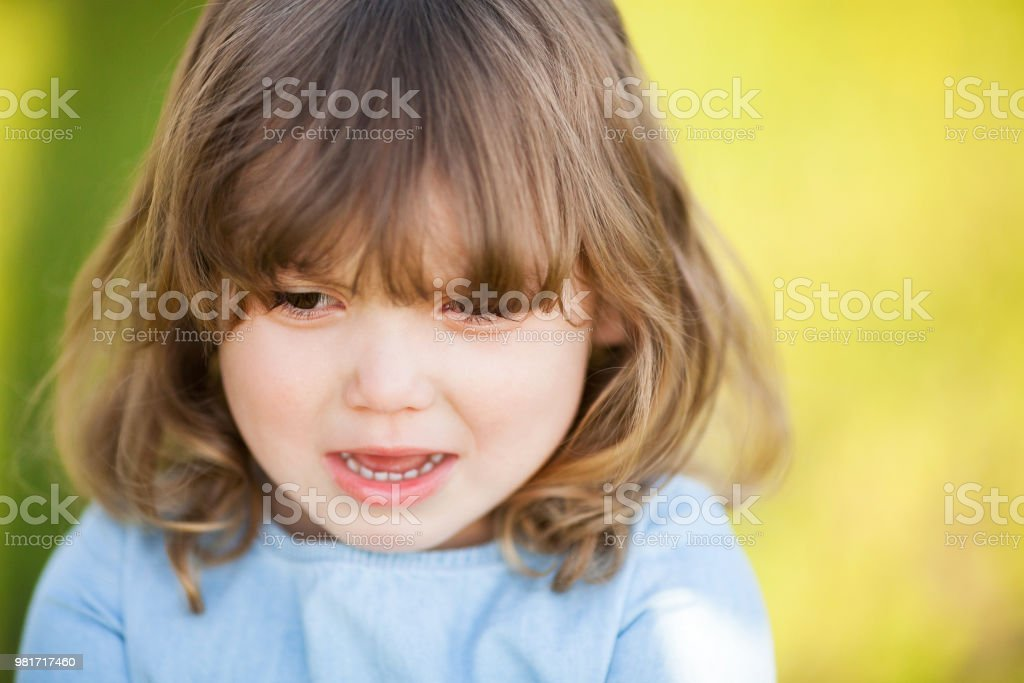 Adorable unhappy little girl with sad expression of her face, going...