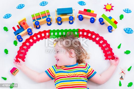 istock Adorable little girl with wooden train 476541574