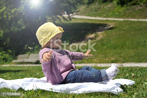 540510130istockphoto Adorable little girl with yellow hat sitting on the grass in the summer. 1170336655