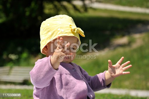 540510130istockphoto Adorable little girl with yellow hat sitting on the grass in the summer. 1170336698