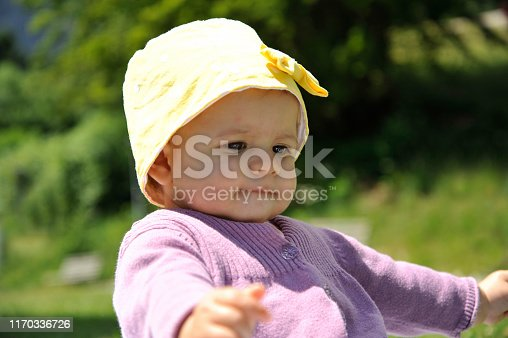 540510130istockphoto Adorable little girl with yellow hat sitting on the grass in the summer. 1170336726