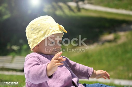 540510130istockphoto Adorable little girl with yellow hat sitting on the grass in the summer. 1170336767