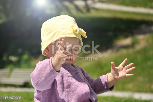 540510130istockphoto Adorable little girl with yellow hat sitting on the grass in the summer. 1171472022
